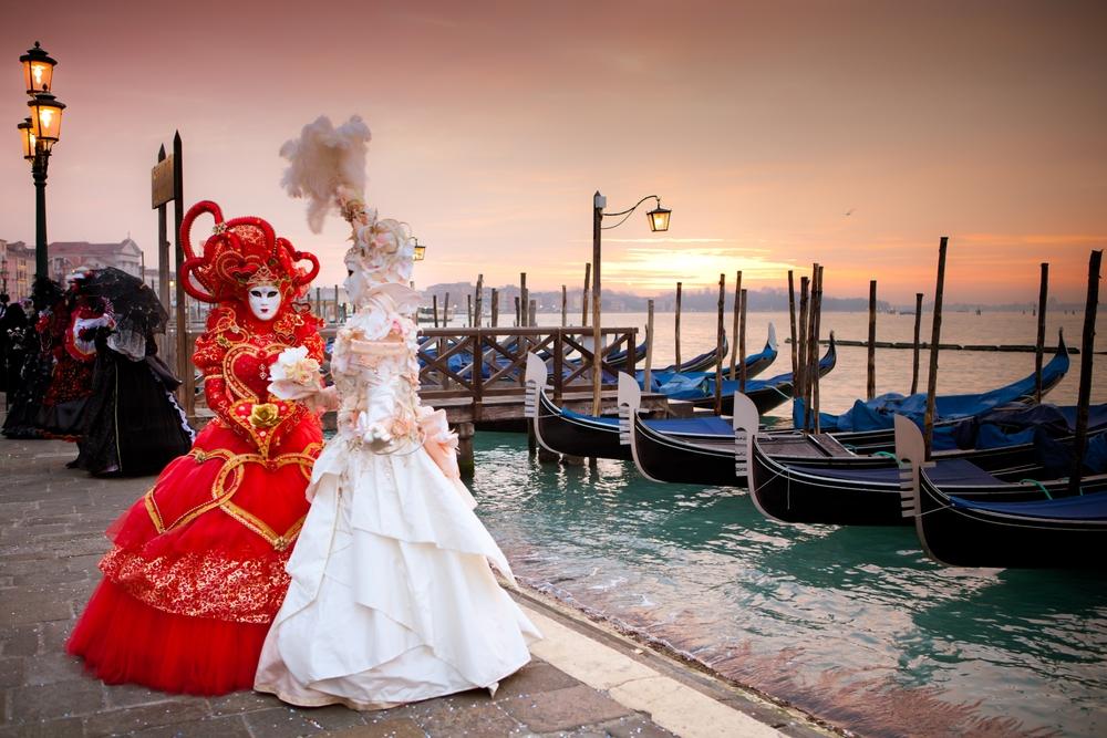 Due maschere in stile settecentesco passeggiano a Venezia guardando le gondole durante il Carnevale